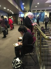 Patrons writing (with the poster art for 'Silence' by Scott McKowen in the background).